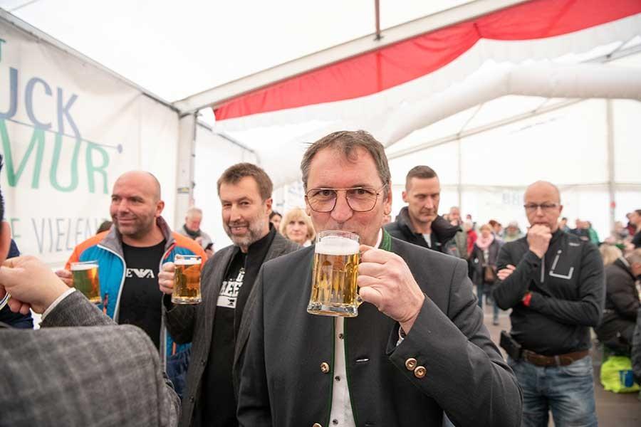 Ein Mann trinkt aus einem Bierglas und sieht dabei in die Kamera.